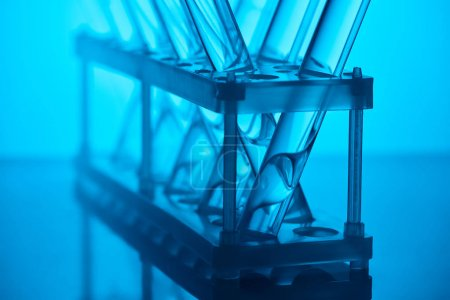 cropped image of glass tubes with liquid on stand in laboratory on blue