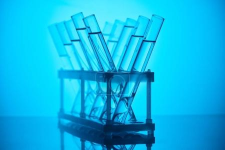 glass tubes with liquid on stand for chemical test on blue