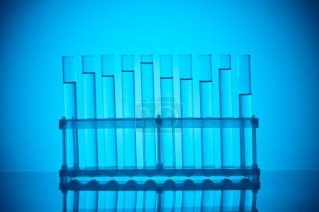 Photo for Row of glass tubes with liquid on stand on blue - Royalty Free Image