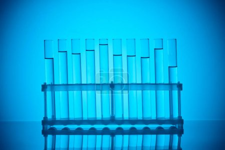 row of glass tubes with liquid on stand on blue