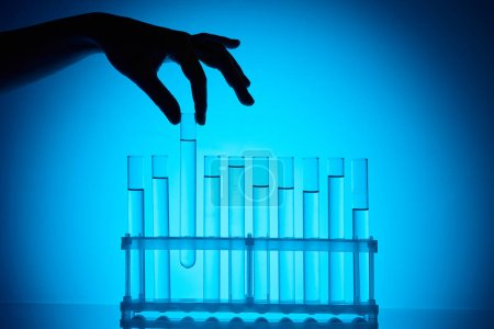 cropped image of chemist taking glass tube from stand on blue