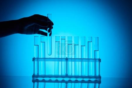 cropped image of female chemist taking glass tube from stand on blue