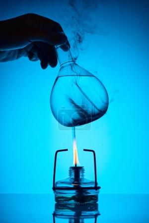 cropped image of chemist warming up substance for analysis on blue