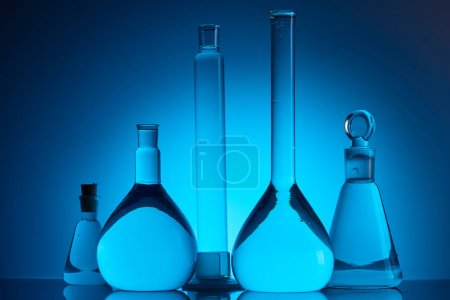 different glass flasks with liquid in chemical laboratory on blue
