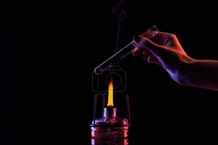 cropped image of chemist warming up tube with liquid on black