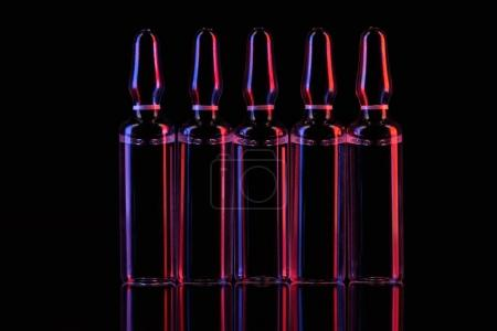 row of transparent glass ampoules with liquid on table on black
