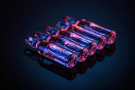 Photo pour Rangée d'ampoules en verre transparent avec liquide sur la table - image libre de droit