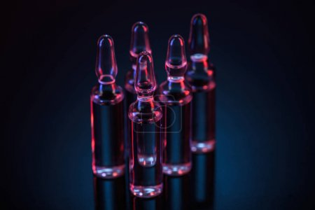 five transparent glass ampoules with substance on table