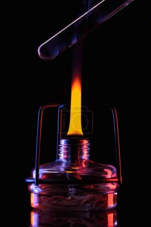 heating tube with liquid in laboratory on black