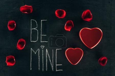 Photo for Lettering BE MINE surrounded with rose petals and heart boxes on black surface, st valentines day concept - Royalty Free Image