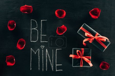 lettering BE MINE surrounded with rose petals and gift boxes on black surface