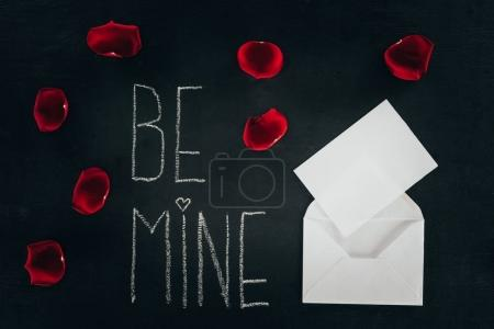 lettering BE MINE surrounded with rose petals and envelope on black surface, st valentines day concept