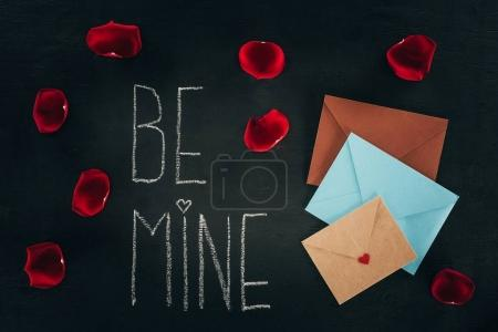 lettering BE MINE surrounded with rose petals and envelopes on black surface, st valentines day concept