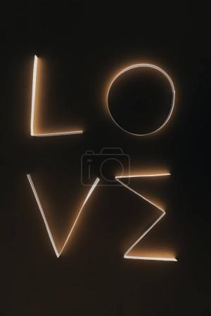 word LOVE made of paper stripes on dark surface