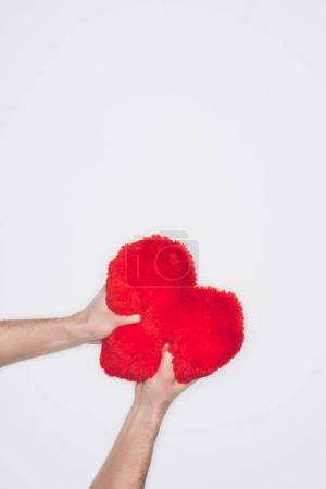 cropped shot of angry man squeezing soft red heart pillow isolated on white