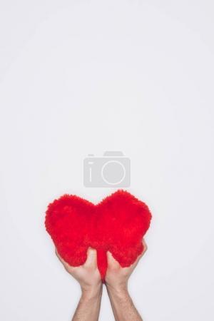 Foto de Tiro corto del hombre apretando la almohada suave corazón rojo aislado en blanco - Imagen libre de derechos