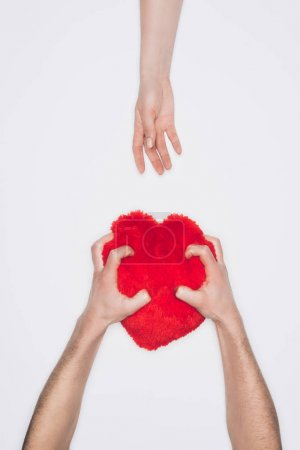 cropped shot of man squeezing red heart pillow while woman reaching for it isolated on white