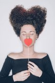 attractive young woman with curly hair covering mouth with red heart isolated on white, st valentines day concept