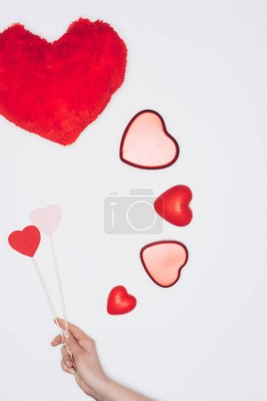 cropped shot of woman holding hearts on sticks near valentines holiday composition isolated on white