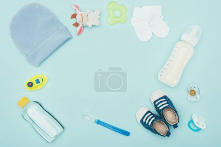 Photo for Top view of baby clothes, accessories and milk isolated on blue - Royalty Free Image