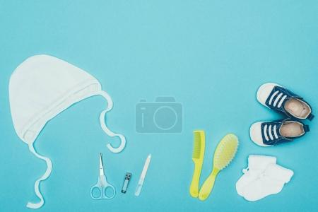 top view of baby clothes and accessories isolated on blue