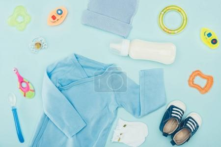 Photo for Top view of baby clothes and accessories with milk isolated on blue - Royalty Free Image