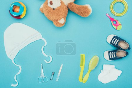 top view of teddy bear and baby clothes with equipment isolated on blue