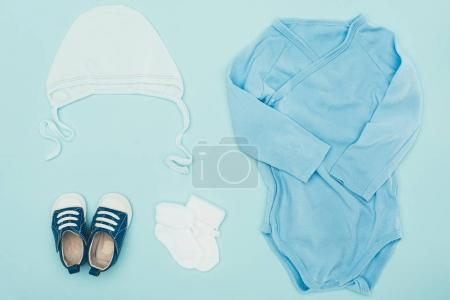 top view of baby clothes isolated on blue