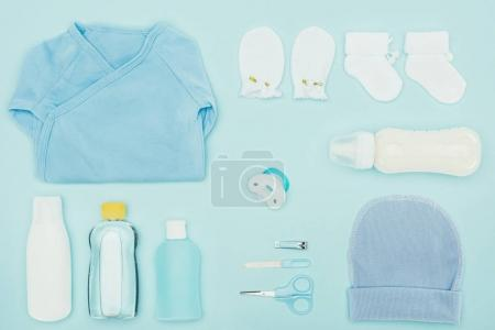 top view of baby clothes and bathroom accessories isolated on blue