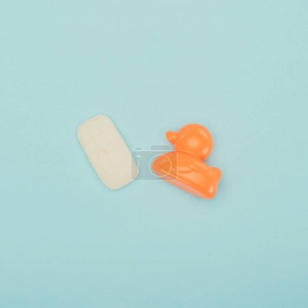 top view of soap and baby duck toy isolated on blue