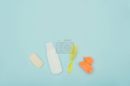 top view of baby toy and bathroom accessories isolated on blue