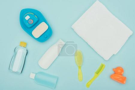 top view of baby toys and bathroom accessories scattered isolated on blue