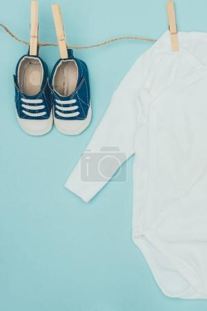 top view of baby bodysuit and shoes drying on rope isolated on blue