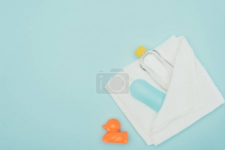 top view of bathroom accessories in towel and rubber duck isolated on blue