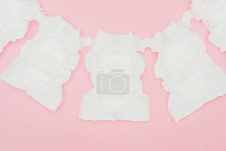 top view of clean unused baby diapers isolated on pink