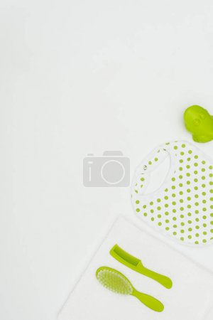 top view of baby bib with towel and combs isolated on white
