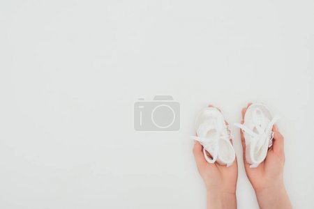 cropped image of woman holding white baby shoes isolated on white