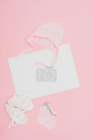 top view of empty board with baby clothes isolated on pink