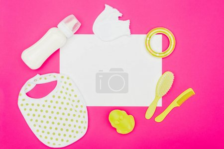 top view of empty board with baby accessories isolated on pink