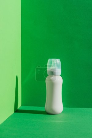 plastic baby bottle with milk on green