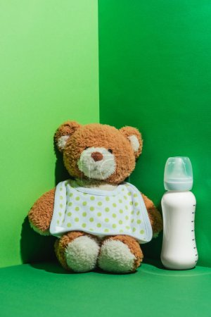teddy bear and baby bottle with milk on green