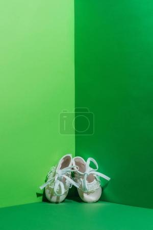 white baby shoes in corner on green