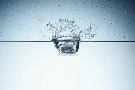 Photo pour Cube de glace dans l'eau avec splash, isolé sur blanc - image libre de droit