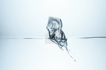 Photo pour Glaçon éclabousser dans l'eau, isolé sur blanc - image libre de droit