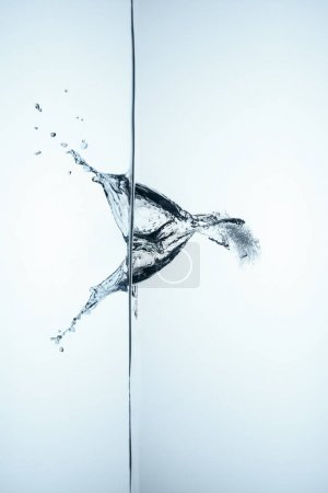ice cube in water with splash and drops, isolated on white