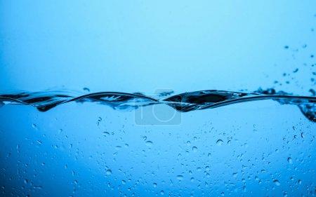 Photo pour Texture de l'eau qui coule avec gouttes, isolées sur les blue - image libre de droit