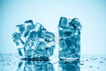 melting ice cubes near glass and in glass, on white with drops