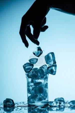 partial view of person throwing ice cubes into glass