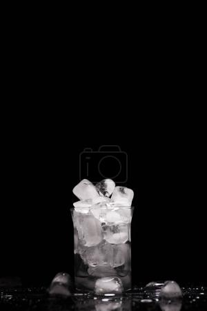 Photo for Melting ice cubes int glass, on black with drops - Royalty Free Image