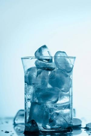 melting ice cubes in glass with drops, on white